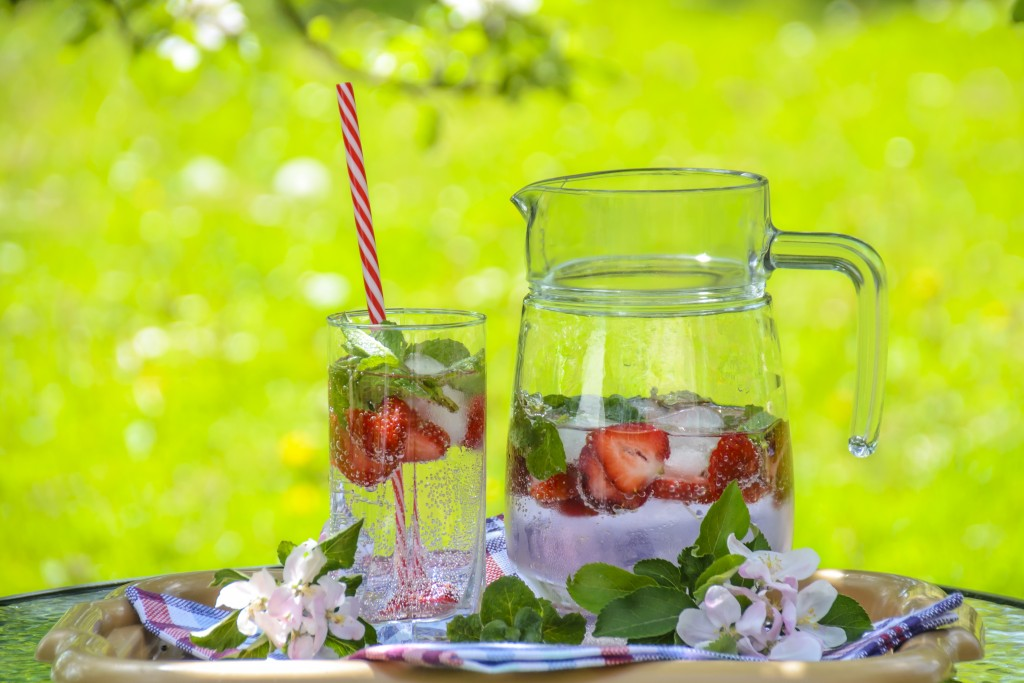 A photograph of a jug and glass on a table. They are filled with ice, strawberries and water. The background shows it is set on a summer's day.